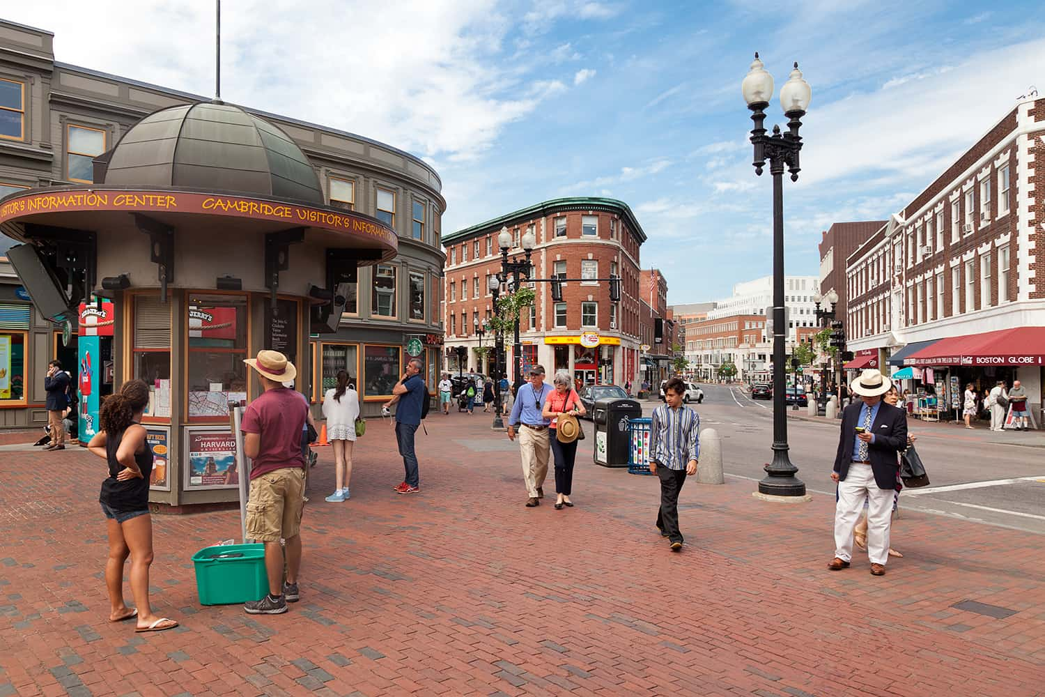 People walk around Harvard Square on a sunny day in Cambridge, MA.