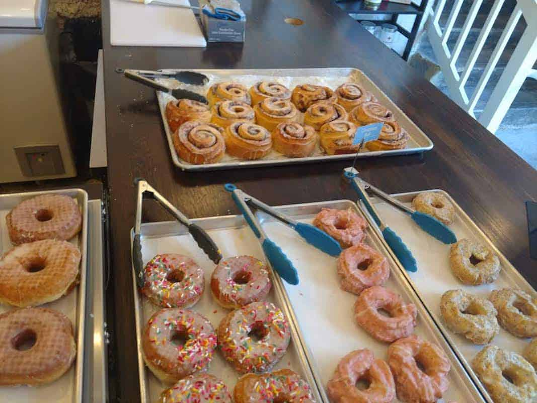 Three trays of various donuts sit on a table with tongs next to each tray.