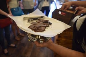 Someone holds a platter full of chocolate bars on Off the Beaten Path Food Tours' Jamaica Plain Vegan Chocolate Tour.