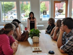 A large group of people sit at a long table listening to a woman talk during an Off the Beaten Path Food Tour in Downtown Lowell.