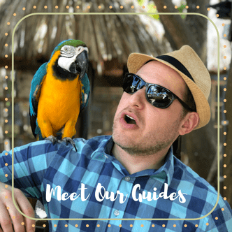 Mark, an Off the Beaten Path Food Tour guide, wears a blue checkered shirt, straw hat, and black sunglasses, while a parrot rests on his shoulder.