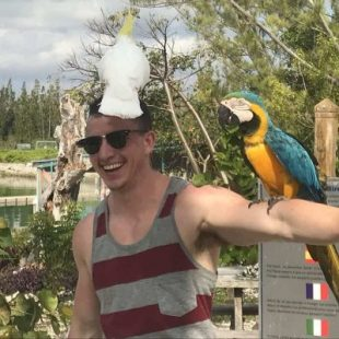 Mitch, an Off the Beaten Path Food Tour guide, wears a striped shirt and has two birds perched on him.