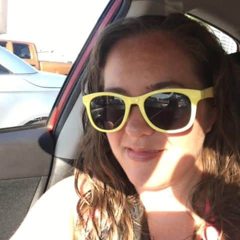 Sydney, an Off the Beaten Path Food Tour guide, wears green sunglasses and smiles while sitting in a car.