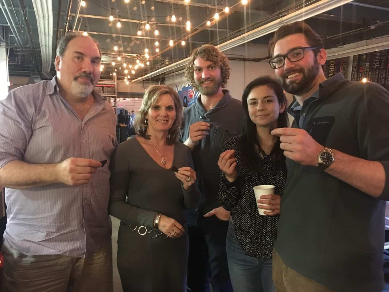 A group of five people smile at the camera while enjoying food on Off the Beaten Path Food Tour's Union Square Food Tour.