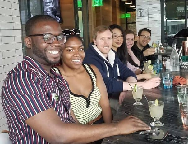 A group of people sit smiling at a table while on an Off the Beaten Path Food Tour.