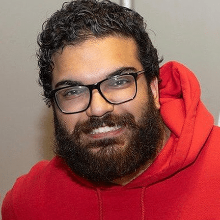 Dev, an Off the Beaten Path Food Tour guide, wears a red sweatshirt, glasses, and a beard.