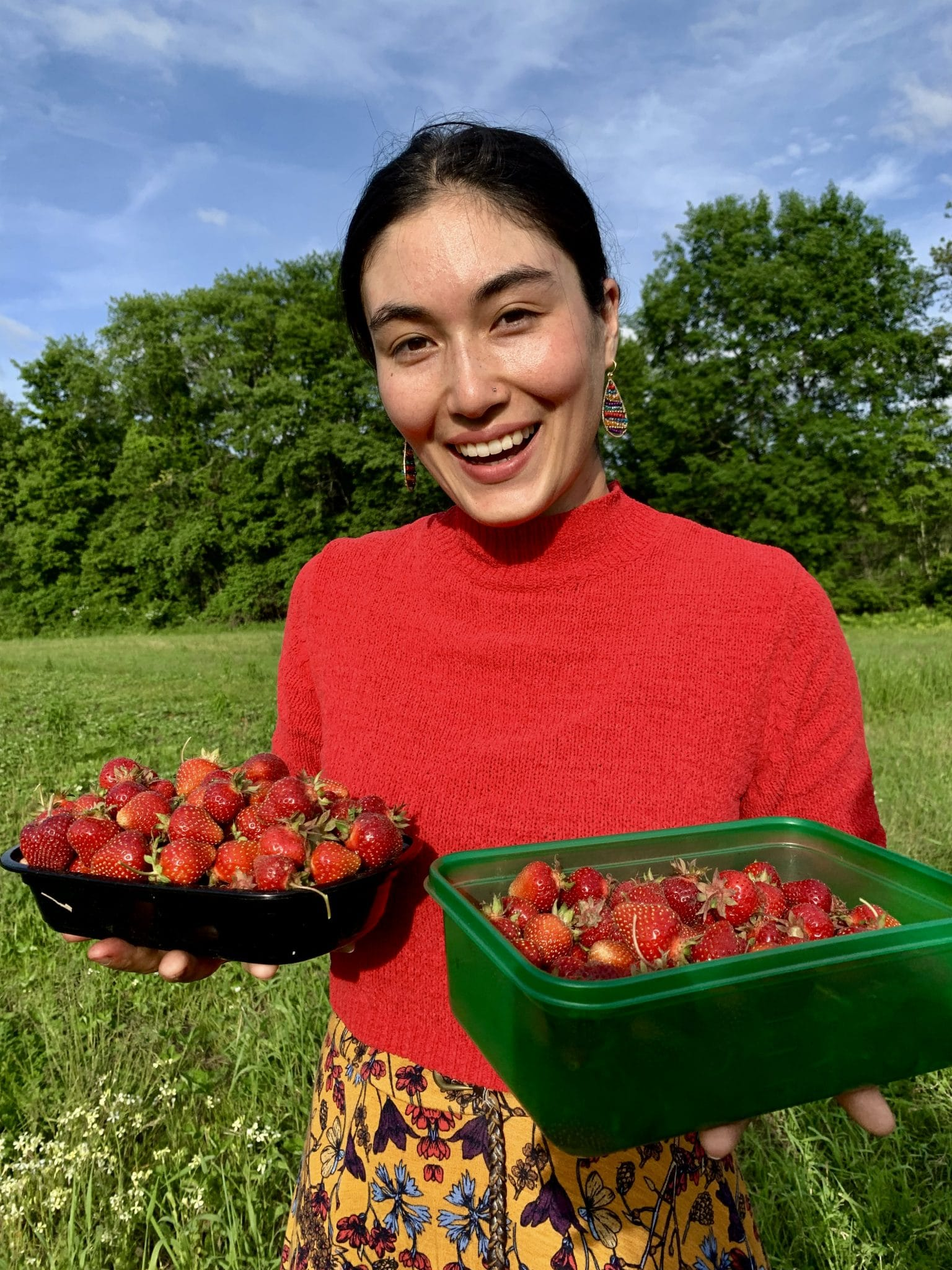 Yun Yun, an Off the Beaten Path Food Tour guide, wears a red shirt while holding strawberries in a field.
