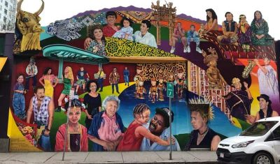 A large colorful mural of various people as seen in Central Square, Cambridge, MA.