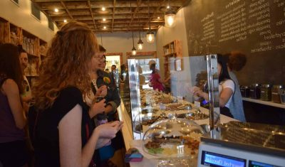 A woman stands in a line at a chocolate shop while on an Off the Beaten Path Food Tour.