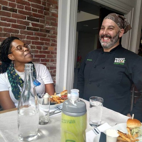 A chef and tour guest laugh while talking to one anotheron Off the Beaten Path Food Tours' Downtown Lowell Food Tour.