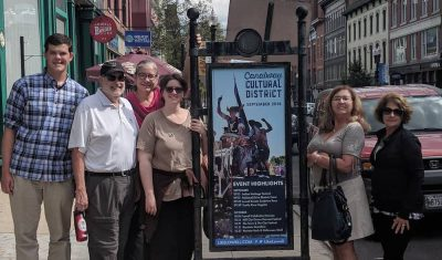 A group of people stand next to a sign in downtown Lowell, MA.