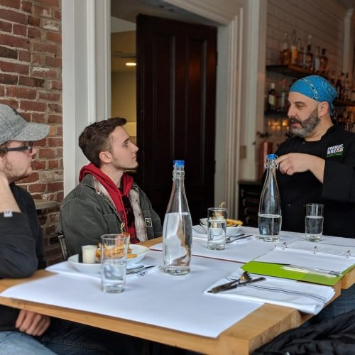 A chef and two guests talk about food whileon Off the Beaten Path Food Tours' Downtown Lowell Food Tour.