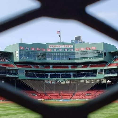 Fenway Park in Boston as seen through a chainlink fence.