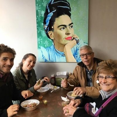 A group of people sit enjoying food at a table with a large mural of Frida Kahlo in the background.