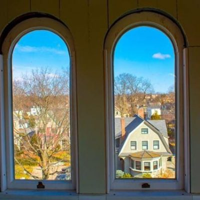 Blue skies and winter trees as seen through arched windows.