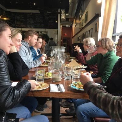A group of people sit at a table enjoying food while onOff the Beaten Path Food Tours' Jamaica Plain Food Tour.