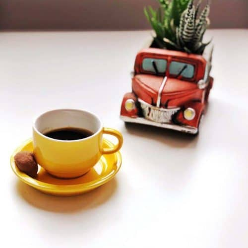 A yellow espresso cut sits on a white table next to a miniature red car.