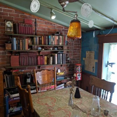 The interior of a cozy cafe with a brick wall with bookshelves and a table with chairs.