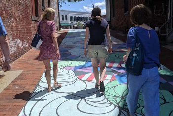 Three women walk over an art mural painted on the street while enjoying an Off the Beaten Path Food Tour in Northampton.