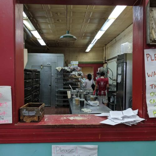 A bakery window that is red and blue as seen on Off the Beaten Path Food Tours' Roslindale Food Tour.