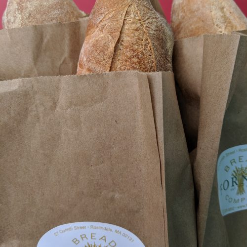 A baguette in a paper bag as seen on Off the Beaten Path Food Tours' Roslindale Food Tour.