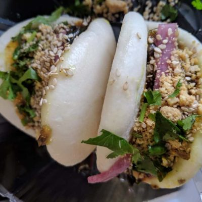 Two overloaded bao buns sit on a plate.