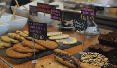 Cookies and various pastries are displayed at a local cafe behind glass as seen on Off the Beaten Path Food Tour's Jamaica Plain Vegan Chocolate Tour.