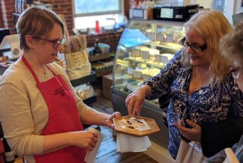 A woman in an apron offers another woman a sample of cheese at Lowell Mill No. 5 in Lowell, MA.