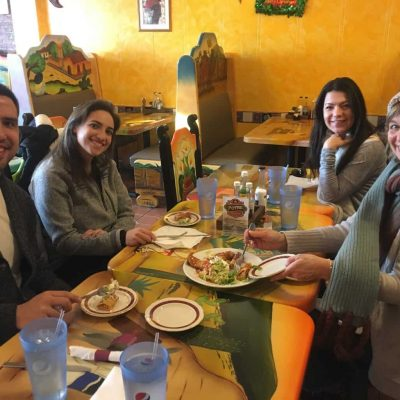 A group of people smile at the camera while enjoying Mexican food at El Potro in Union Square, Somerville.